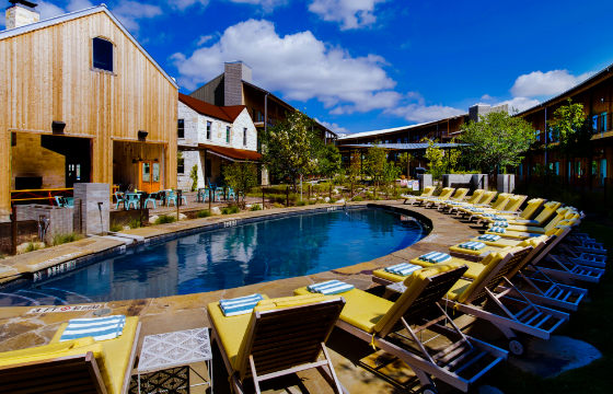 Outdoor pool and lounge chairs at Lone Star Court in Austin, Texas